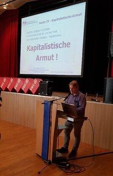Carsten Samoticha stellt eine Präsentation des Erwerbslosenausschusses vor.